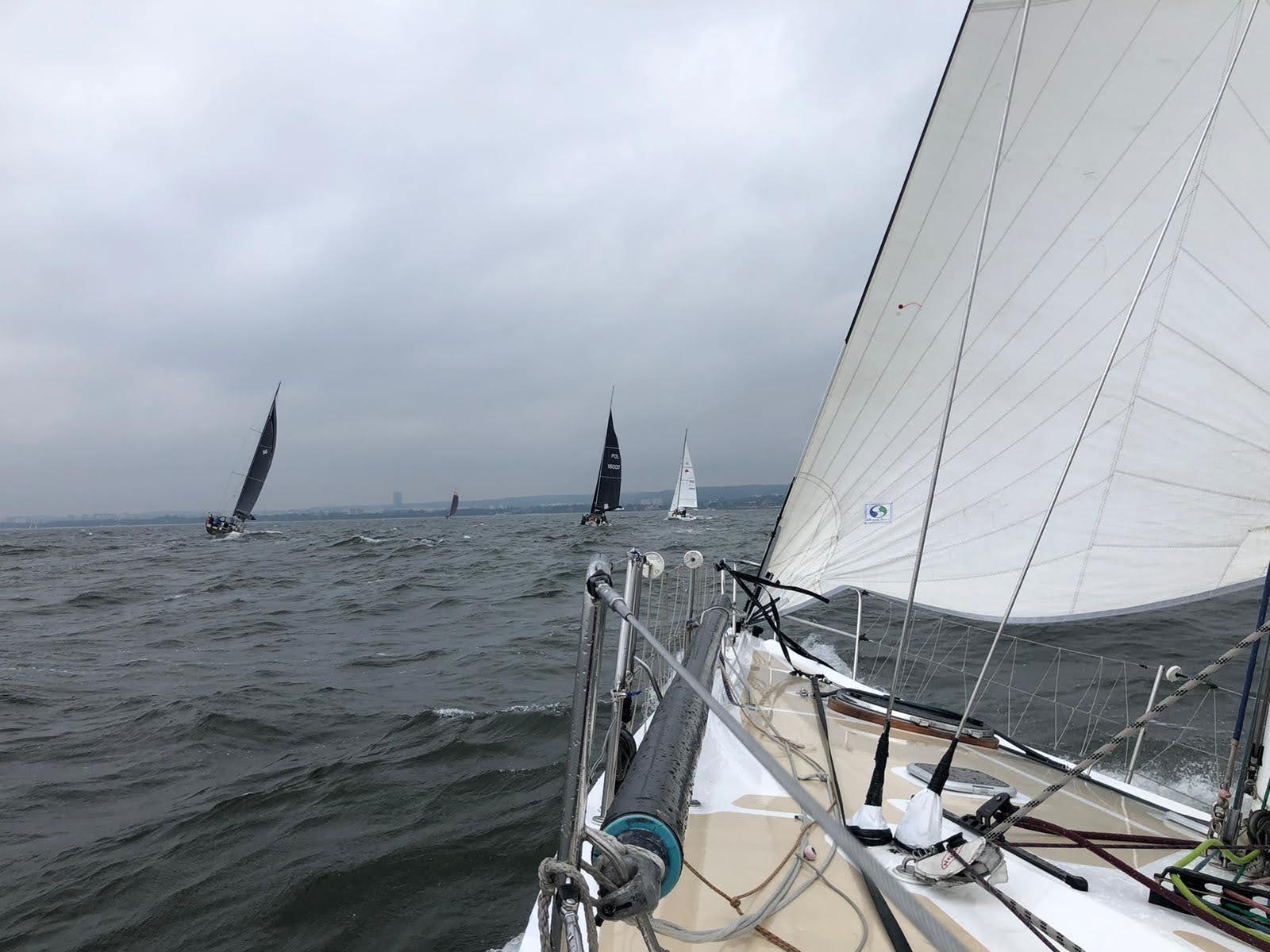 Team 10BFT opisuje: nad pokładem dziobowym jachtu pracuje fok. W oddali widać cztery inne jachtu i Gdynię